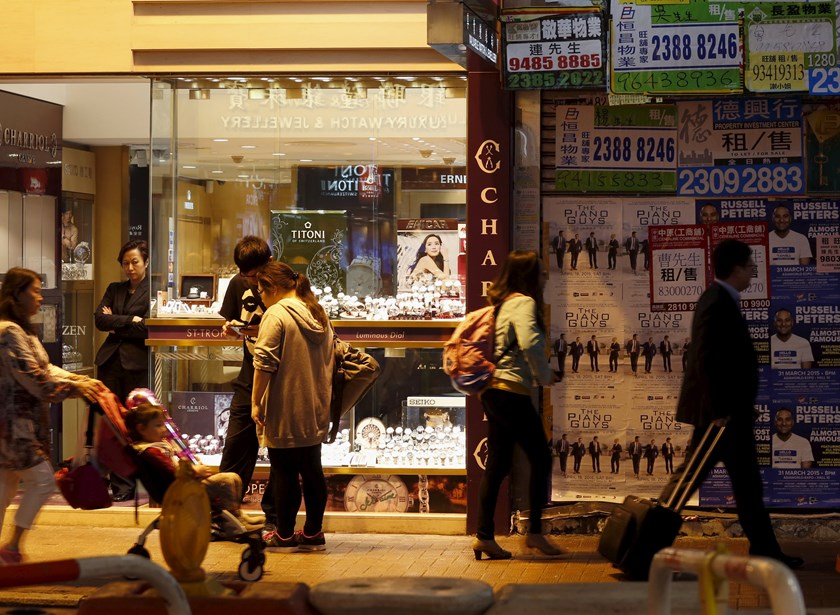 A sales attendant (2nd L) at a watch and jewelry store waits for customers next to a shop for rent at Causeway Bay shopping district in Hong Kong March 26, 2015. Photo: Reuters
