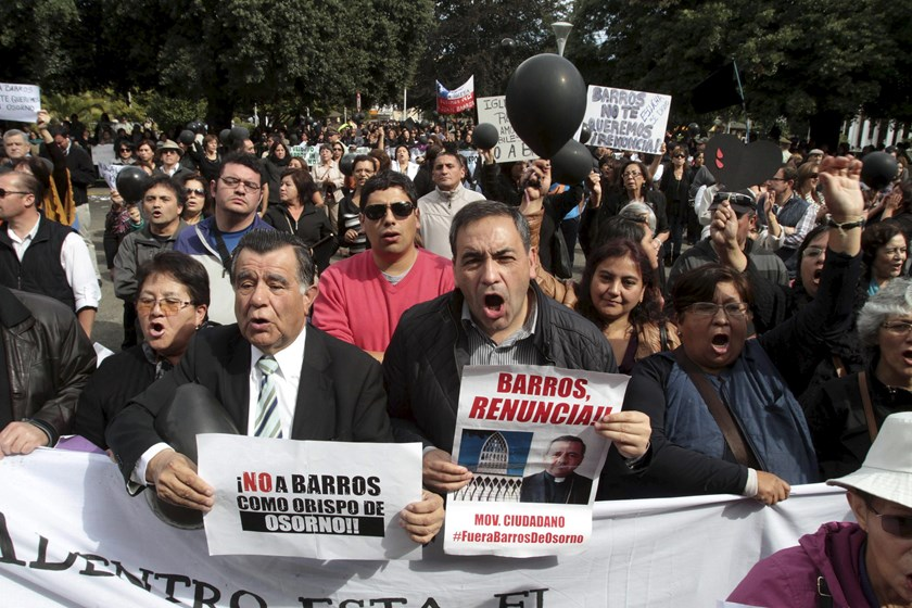 Chilean Deputy Fidel Espinoza (R) and citizens protest as Bishop Juan Barros (not pictured) attends his first religious service inside the Osorno cathedral, south of Santiago, March 21, 2015. REUTERS/Carlos Gutierrez