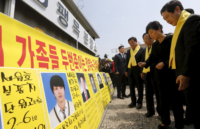 South Korean President Park Geun-hye (2nd R) looks at portraits of missing passengers onboard sunken ferry Sewol during her visit to a port in Jindo, on the occasion of the first anniversary of the ferry disaster. Photo: Reuters