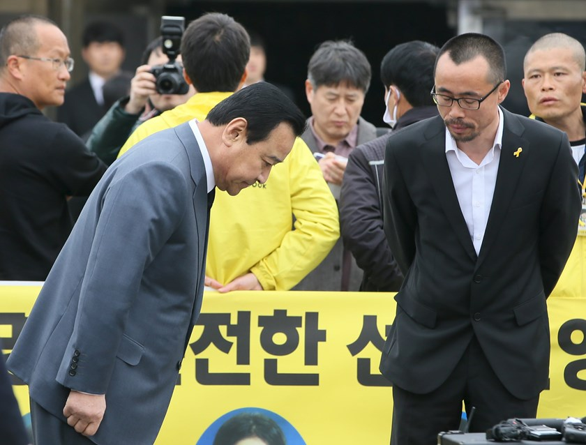 South Korean Prime Minister Lee Wan-koo (L) bows to a relative (R) of a victim onboard sunken ferry Sewol, at the official memorial altar for the victims in Ansan on the occasion of the first anniversary of the ferry disaster that killed more than 300 pas
