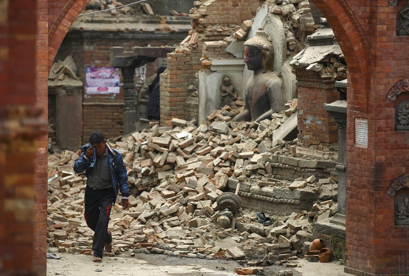 A man cries as he walks on the street while passing through a damaged statue of Lord Buddha a day after an earthquake in Bhaktapur, Nepal April 26, 2015. Rescuers dug with their bare hands and bodies piled up in Nepal on Sunday after the earthquake devast