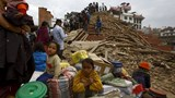 People sit with their belongings outside a damaged temple in Bashantapur Durbar Square after a major earthquake hit Kathmandu, Nepal April 25, 2015. A shallow earthquake measuring 7.9 magnitude struck west of the ancient Nepali capital of Kathmandu on Sat