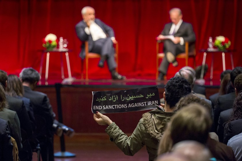 A demonstrator holds up a sign while Iranian Foreign Minister Mohammad Javad Zarif speaks with Washington Post journalist David Ignatius at the New York University (NYU) Center on International Cooperation in New York April 29, 2015. Photo: Reuters