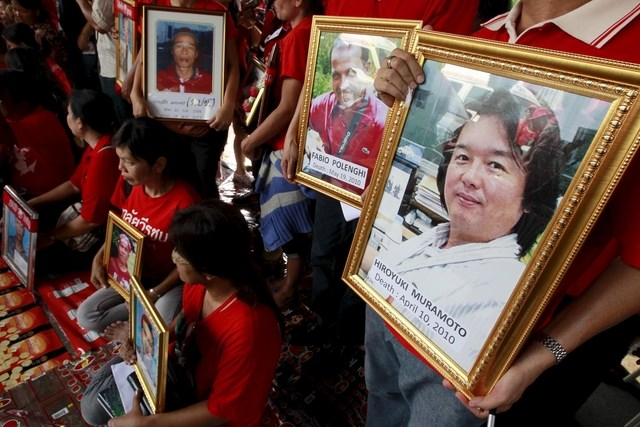 Anti-government ''red shirt'' protesters hold pictures of people who died, including Reuters television cameraman Hiroyuki Muramoto (R) and Italian freelance photographer Fabio Polenghi (2nd R), during a religious ceremony. Photo: Reuters