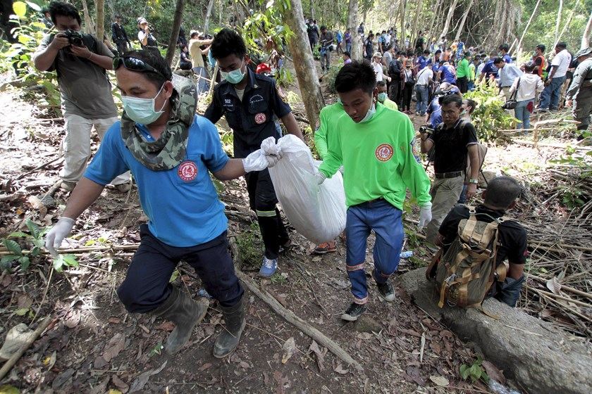 Rescue workers carry a body bag with remains retrieved from a mass grave at an abandoned camp in a jungle some three hundred meters from the border with Malaysia, in Thailand's southern Songkhla province May 2, 2015. Photo: Reuters