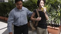 Amos Yee eats a banana as he arrives with his father to the State Courts for a pre-trial conference in Singapore April 17, 2015. Photo: Reuters