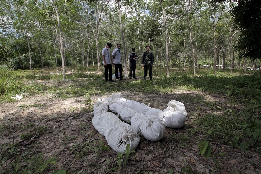 Policemen take notes behind human remains retrieved from a mass grave at a rubber plantation near a mountain in Thailand's southern Songkhla province May 6, 2015. Photo: Reuters