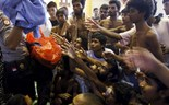 An Indonesia policeman distributes used clothes to migrants believed to be Rohingya inside a shelter in Lhoksukon, Indonesia's Aceh Province May 11, 2015. Photo: Reuters