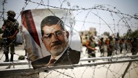 A portrait of deposed Egyptian President Mohamed Mursi is seen on barbed wire outside the Republican Guard headquarters in Cairo, in this file picture taken July 6, 2013. Photo: Reuters