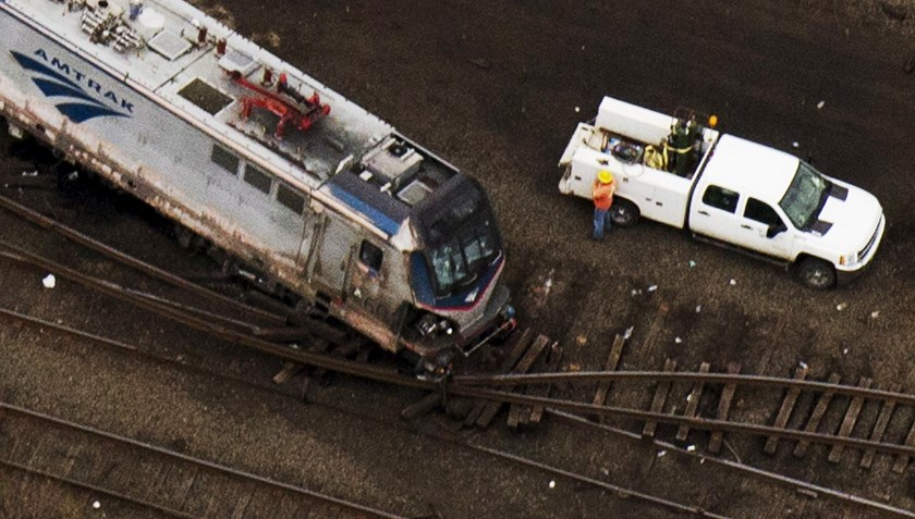 Emergency workers look through the remains of a derailed Amtrak train in Philadelphia, Pennsylvania in this May 13, 2015 file photo.