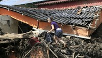 A woman climbs the debris of a destroyed house, after a landslide sent mud and water crashing onto homes close to the municipality of Salgar in Antioquia department, Colombia May 19, 2015. REUTERS/Jose Miguel Gomez