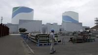 An employee of Kyushu Electric Power Co walks in front of reactor buildings at the company's Sendai nuclear power plant in Satsumasendai, Kagoshima prefecture in this April 3, 2014 file photo. REUTERS/Mari Saito/Files