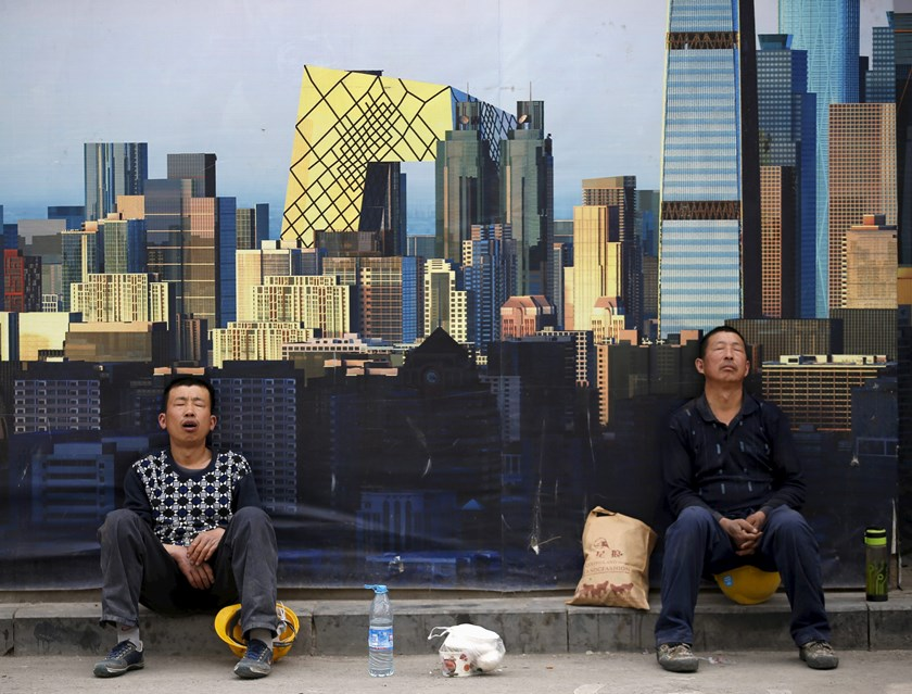 Construction workers take a nap in front of a wall of a construction site during their lunch break in Beijing, China, in this May 5, 2015 file photo. Photo: Reuters