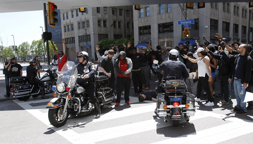 A protestor lies on the ground on a downtown intersection as Cleveland police officers block them from a RTA bus following the not guilty verdict for Cleveland police officer Michael Brelo on manslaughter charges in Cleveland, Ohio, May 23, 2015. Photo: R
