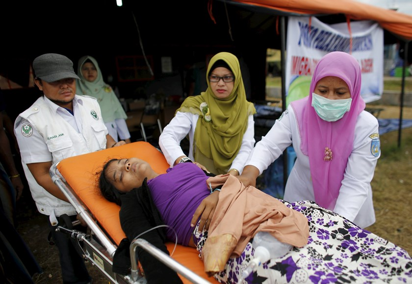 Indonesian health workers move a Rohingya migrant, who arrived recently by boat to an awaiting ambulance at a temporary shelter in Kuala Langsa, in Indonesia's Aceh Province May 25, 2015. Photo: Reuters