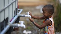 A young Rohingya migrant, who arrived recently by boat, plays with a water tap at a temporary shelter in Kuala Langsa, in Indonesia's Aceh Province May 25, 2015. Photo: Reuters