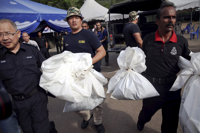 Forensic policemen carry body bags with human remains found at the site of human trafficking camps in the jungle close the Thailand border after they brought them to a police camp near Wang Kelian in northern Malaysia May 25, 2015. Photo: Reuters