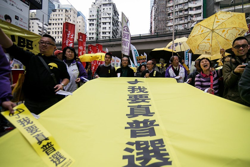 "Protesters hold yellow umbrellas and a banner reading ""We Want Universal Suffrage"" during a pro-democracy rally in Hong Kong, on Feb. 1. Photo: Bloomberg"
