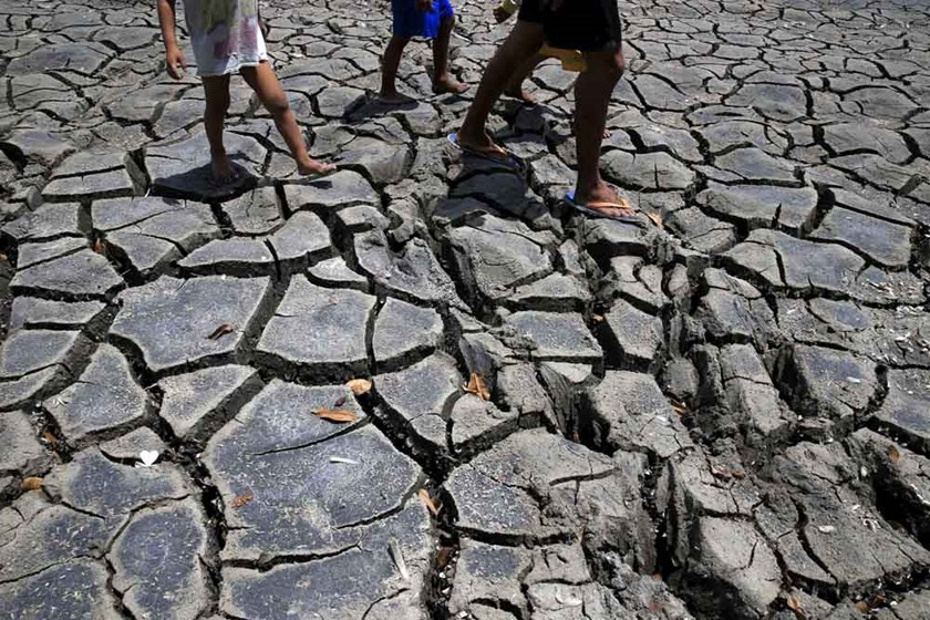 Residents walk over the cracked soil of a 1.5 hectare dried up fishery at the Novaleta town in Cavite province, south of Manila May 26, 2015. Photo: Reuters