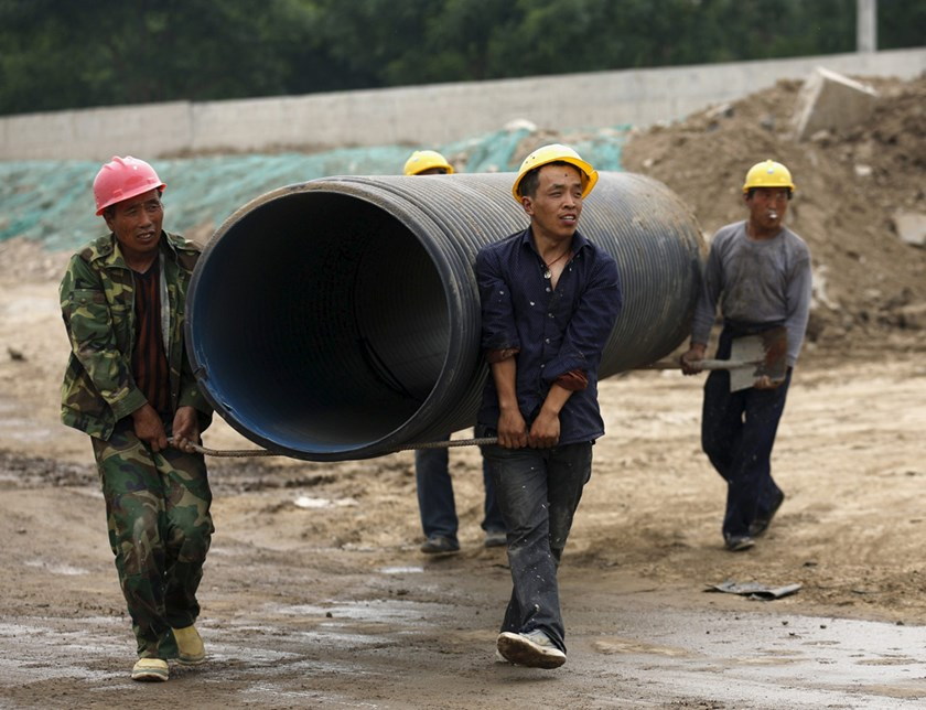 Workers carry a big pipe at a construction site for building a new road on the outskirts of Beijing, China, May 13, 2015. Photo: Reuters