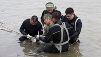 A woman is helped after being pulled out by divers from a sunken ship in Jianli, Hubei province, China, June 2, 2015. Photo: Reuters