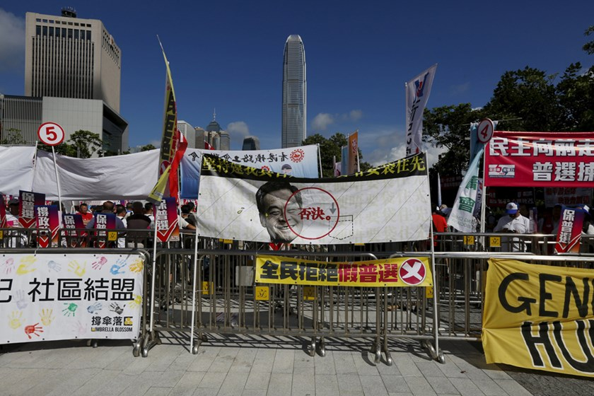 A banner featuring a portrait of Hong Kong Chief Executive Leung Chun-ying with a veto sign set up by pro-democracy protesters, is displayed in front of a pro-China rally outside Legislative Council in Hong Kong, China, June 18, 2015. Photo: Reuters