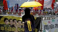 A pro-democracy protester carrying a yellow umbrella, symbol of the Occupy Central movement, stands facing banners set up by pro-China supporters during a rally outside Legislative Council in Hong Kong, China June 18, 2015. Photo: Reuters