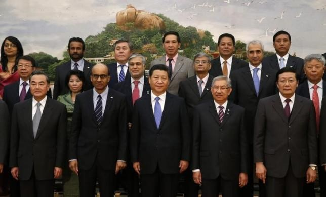 China's President Xi Jinping (front C) poses for photos with guests at the Asian Infrastructure Investment Bank launch ceremony at the Great Hall of the People in Beijing October 24, 2014. REUTERS/TAKAKI YAJIMA/POOL/FILES