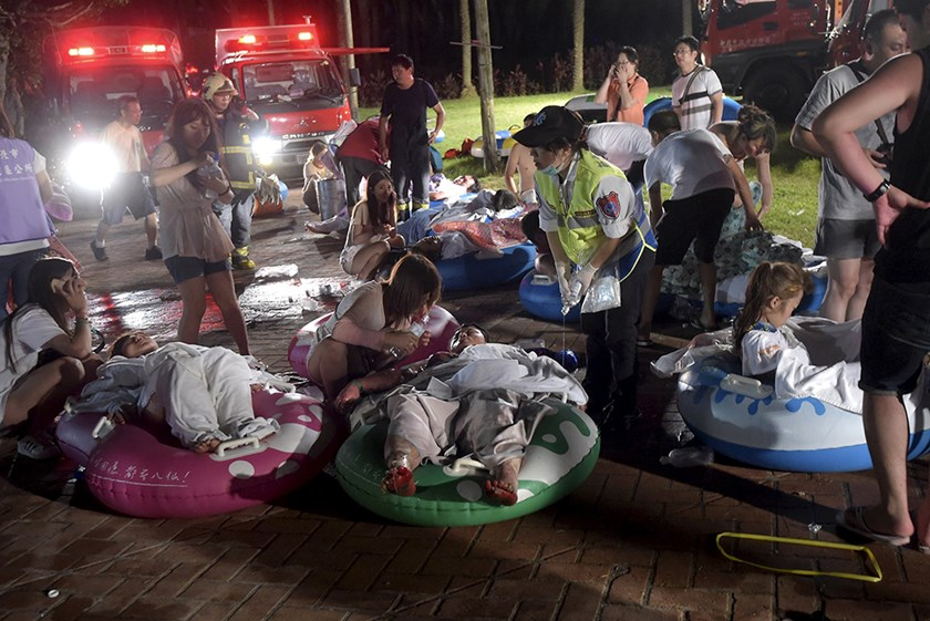 Injured victims from an accidental explosion during a music concert lie on the ground at the Formosa Water Park in New Taipei City, Taiwan, June 27, 2015. REUTERS/Wang Wei