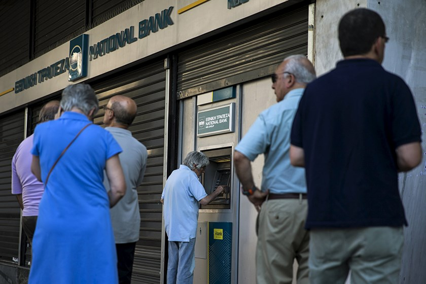 People line up at an ATM outside a National Bank branch in Athens, Greece June 28, 2015. REUTERS/Marko Djurica