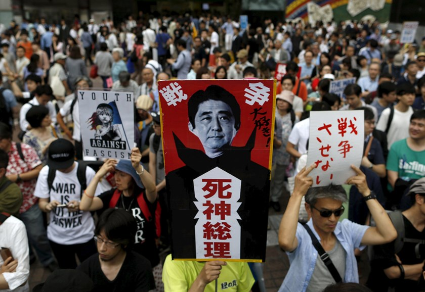 "Protesters holding placards participate in a rally against Japanese Prime Minister Shinzo Abe's administration in Tokyo, Japan, June 27, 2015. Hundreds of people joined the demonstration on Saturday against Abe's policies in Tokyo's Shibuya area. The placard (C) reads in Japanese, ""Love the war"" (top) and ""Reaper Prime Minister"" (bottom). Photo: Reuters"