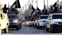 Islamic State fighters parade through Raqqa, Syria in June. Photo: Reuters