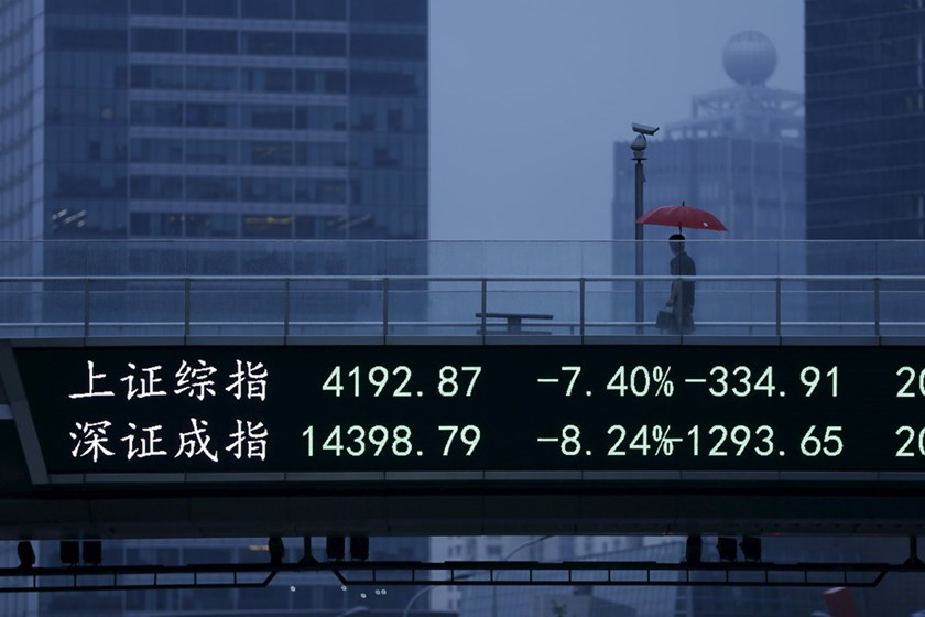 A man walks past an electronic board showing the benchmark Shanghai and Shenzhen stock indices, on a pedestrian overpass at the Pudong financial district in Shanghai, China, June 26, 2015. Photo: Reuters