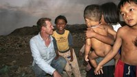 Former Hollywood film executive Scott Neeson is seen with local children who scavenge at the Steung Meanchey trash dump outside Phnom Penh, Cambodia, in this January 2007 photo provided by the subject to Reuters on November 19, 2010.