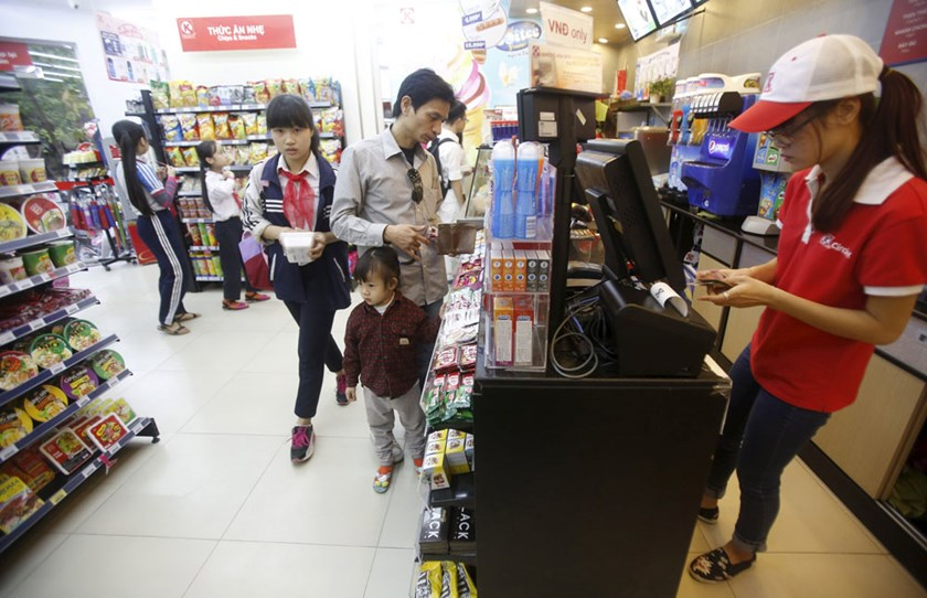 An employee checks a customer's bill inside a Circle-K mart in Hanoi on October 12, 2015. Photo: Reuters