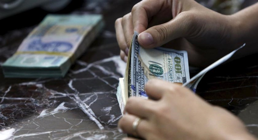 An employee counts U.S. dollar bank-notes near Vietnamese dong bank-notes at a bank in Hanoi. Photo: Reuters