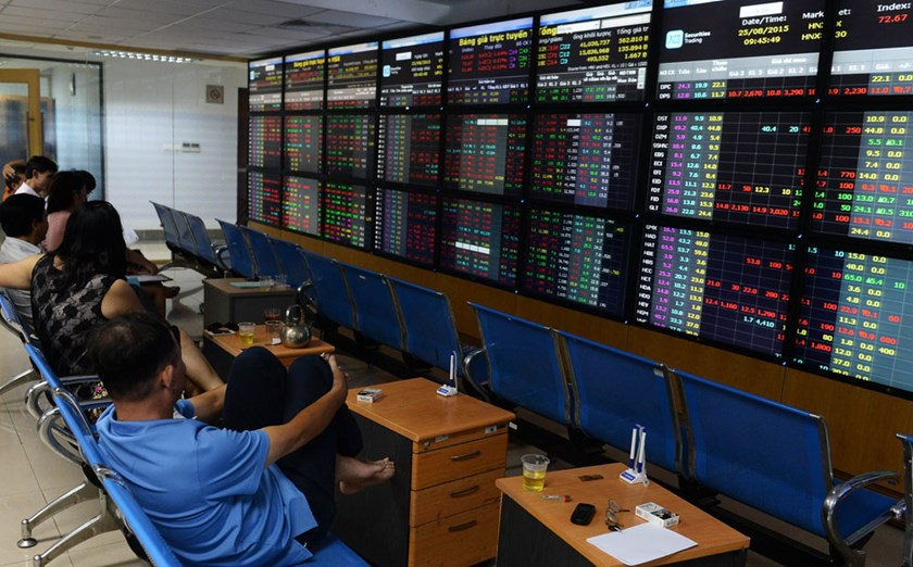 Local investors monitor share prices on an electronic board at a local securities trading floor in Hanoi on August 25, 2015. Photo: AFP/Hoang Dinh Nam