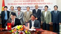 A file photo shows the signing ceremony for the $2.4 billion coal-fired power plant to be built by Malaysian firm Janakuasa