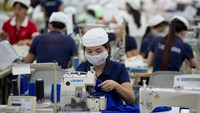 Workers sew clothing with sewing machines at the Esquel Group garment factory at the Vietnam-Singapore Industrial Park in Thuan An, Binh Duong Province on Tuesday, June 3, 2014. Bloomberg/Brent Lewin