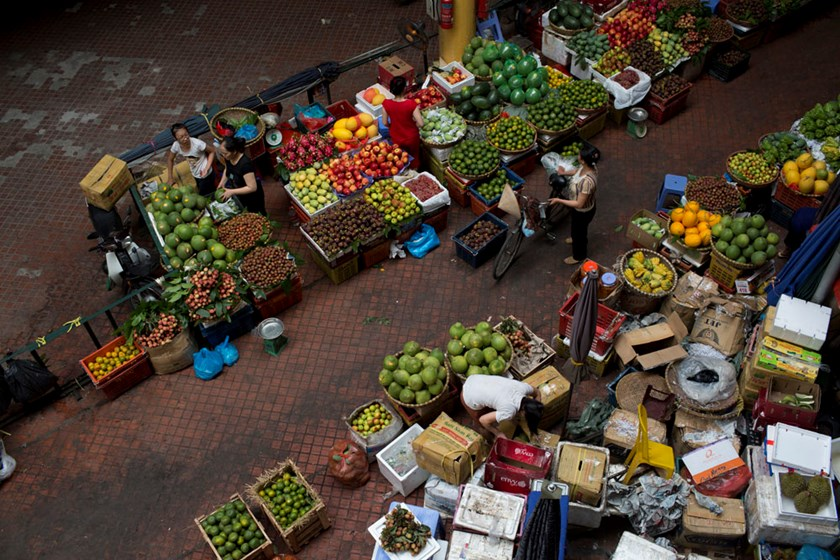 Vendors sell produce at the Cho Hom market in Hanoi on May 31, 2014. Photo: Bloomberg/Brent Lewin