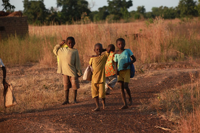 Children walk home along a dirt track in the early evening after leaving class in Benvar, Burkina Faso. Photo: Bloomberg/Chris Ratcliffe