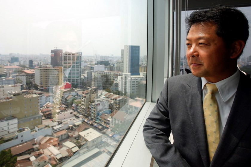 Andy Ho, managing director of asset firm VinaCapital, looks through the window of his office as he poses for a picture in Ho Chi Minh City on March 9, 2015. Photo: Reuters/Kham