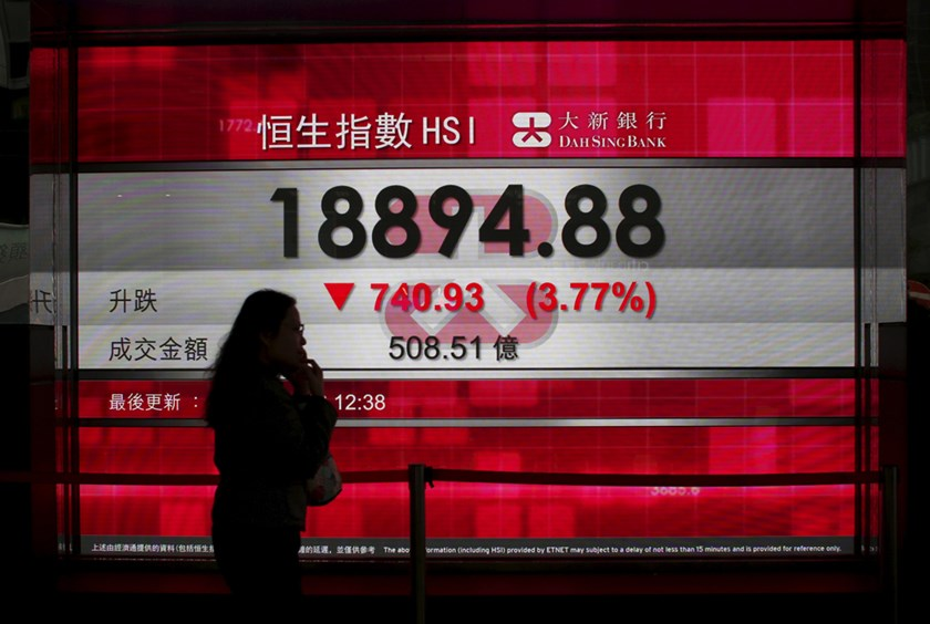 A woman talking on a mobile phone walks past a panel displaying the midday Hang Seng Index in Hong Kong, China January 20, 2016. Photo: REUTERS/Bobby Yip