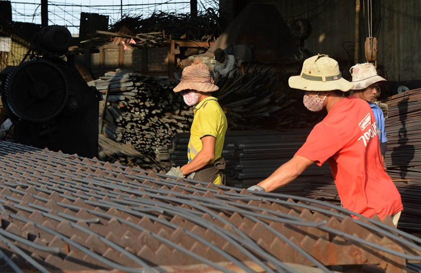 This picture taken on November 14, 2014 shows men working at a private steel workshop which produces steel rods for construction from scrap iron in the Dong Anh district on the outskirts of Hanoi.