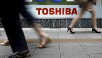 Pedestrians walk past a logo of Toshiba Corp outside an electronics retailer in Tokyo September 14, 2015. Photo: