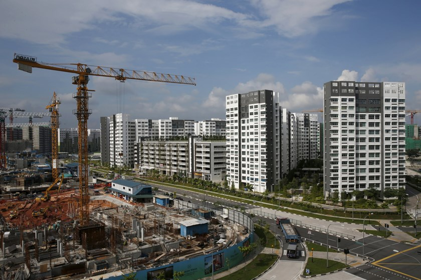 Workers operate cranes at an executive condominium construction site next to completed public housing apartments in Singapore on January 19, 2016.  Singapore is the eighth least-corrupt nation in the world, according to Transparency International's annual survey. Photo: Reuters/Edgar Su