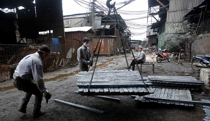 Men load pieces of steel at a steel factory in Chau Khe village, outside Hanoi on December 4, 2014. Photo: Reuters/Kham