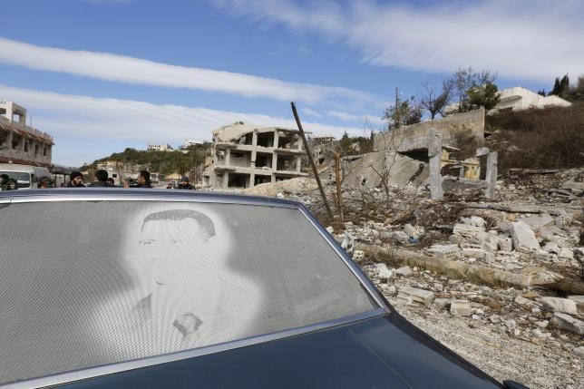 An image of Syria's President Bashar al-Assad is seen on a car parked in front of damaged buildings in the town of Rabiya, after pro-government forces recaptured the rebel-held town in coastal Latakia province, Syria January 27, 2016.