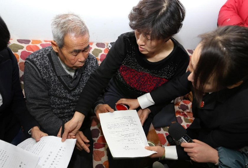 The judge of the higher people's court delivers retrial files to Hugjiltu's parents (C) in Hohhot, northern China's Inner Mongolia autonomous region on December 15, 2014. AFP