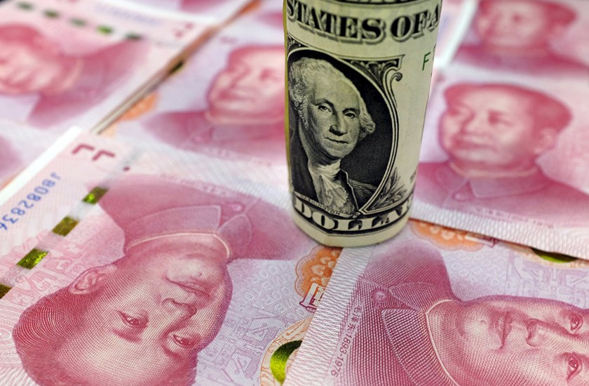 A U.S. one-dollar banknote and Chinese 100-yuan banknotes are seen in this picture illustration, in Beijing, China, January 21, 2016. REUTERS/Jason Lee